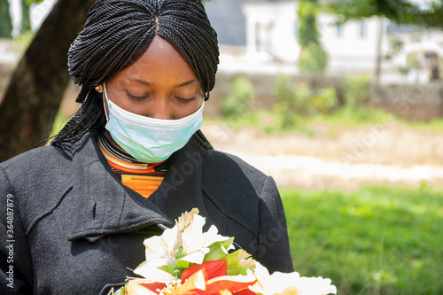 african woman mourning, wearing black and holding flowers Canvas Print