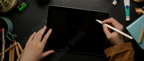 Photo Female designer drawing on digital tablet with stylus pen on dark worktable with