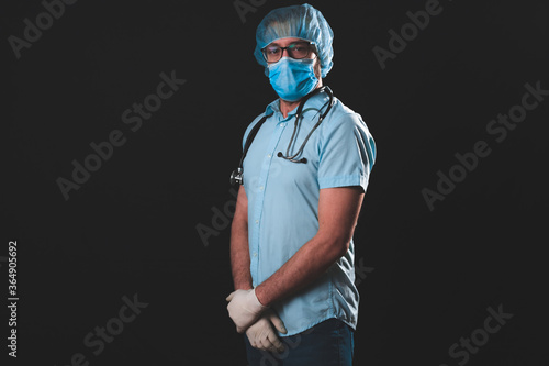 Medical doctor, nurse, surgeon, psychologist working with protective mask, glasses and gloves helping people in the days of panic, pandemic - studio shot on black background.
