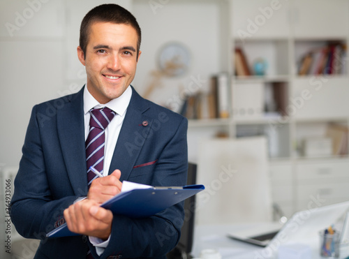 Fotografie, Obraz Portrait of positive business man with folder of documents at office