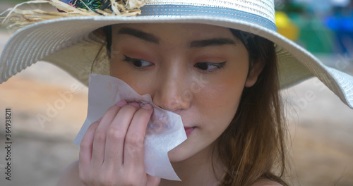 Young woman use oil paper absorbing oil from face. Wallpaper Mural
