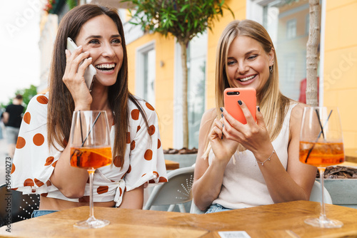 Obraz na plátně Image of women laughing and using cellphones while drinking cocktails