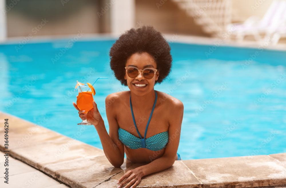Fototapeta Portrait of carefree black woman in swimsuit with cocktail drink at pool on tropical resort