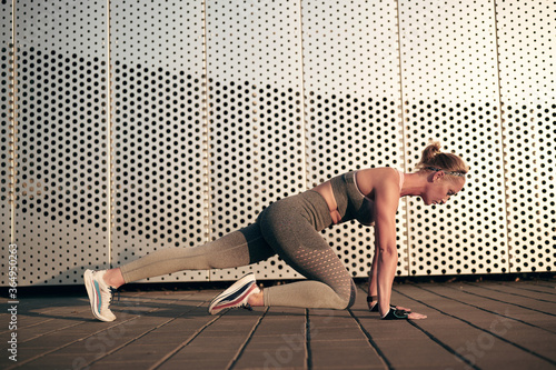 Fototapeta Strong fitness woman is doing mountain climber exercises in front of wall outdoo