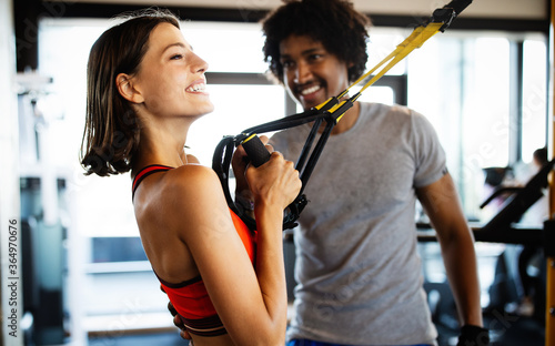 Young beautiful woman doing exercises with personal trainer Billede på lærred