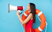Lifeguard Woman Over Isolated Blue Background With Lifeguard Equipment And Shouting Through A Megaphone