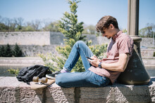 Side View Of Man Sitting On Stone And Looking At Phone. Portrait Of Man Resting On Stone Fence Near Skateboard While Chatting On Mobile.