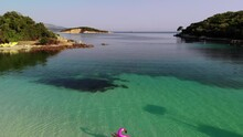 Young Relaxed Woman In A Swimsuit Swims In The Water On An Inflatable Flamingo And Sunbathes. A Drone Flies Backwards Showing A Turquoise Lagoon And Beach. Ksamil, Albania.