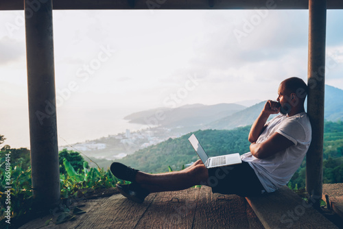 Thoughtful young man looking away on beautiful nature landscape while sitting with laptop computer outdoors Fotobehang