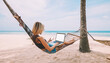 Female freelancer entrepreneur lying on hammock and doing remote business work at modern laptop computer with blank screen area for web page on smartphone during summer vacation on tropical seashore