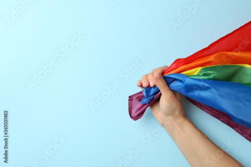 Fototapeta Female hand hold LGBT flag on blue background
