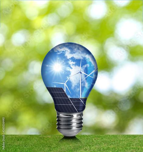 Fototapeta Alternative energy source. Light bulb with solar panels and wind turbines outdoors obraz