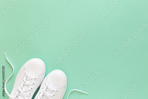 Photo All white sneakers on mint green background. Top view, flat lay