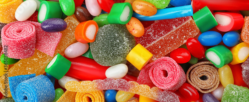 Delicious colorful chewing candies as background, top view. Banner design