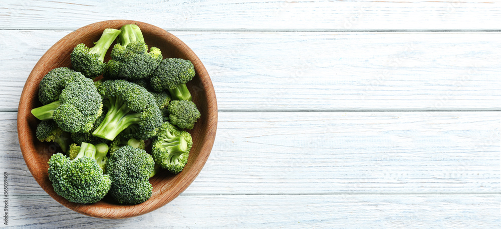 Fototapeta Top view of fresh green broccoli on white wooden table, space for text. Banner design