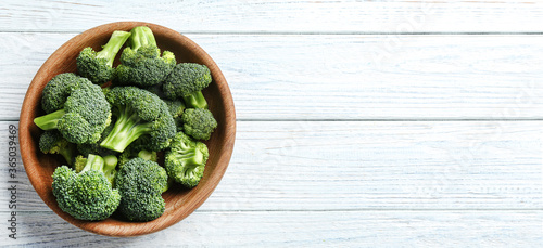 Fototapeta Top view of fresh green broccoli on white wooden table, space for text. Banner design obraz