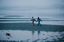 Two Kids Running On Winter Beach
