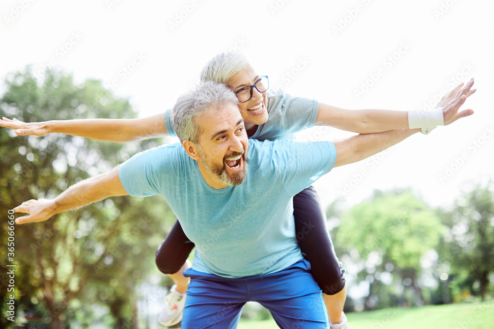Fototapeta outdoor senior fitness woman man lifestyle active sport exercise healthy fit retirement love fun piggyback