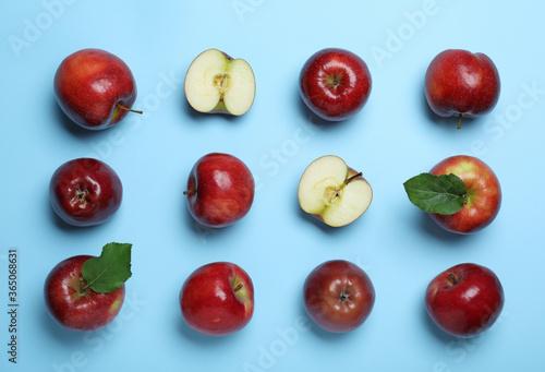 Cuadros en Lienzo Tasty red apples on light blue background, flat lay