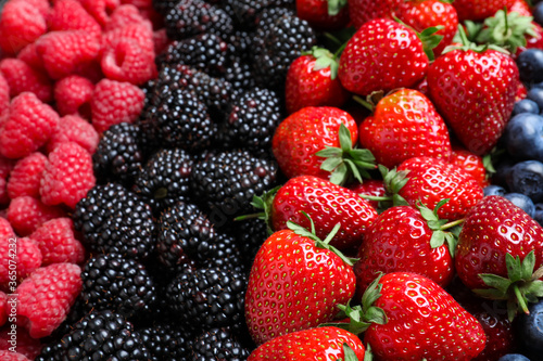 Photo Mix of different ripe tasty berries as background, closeup view