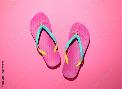 Fototapeta Pair of stylish flip flops on pink background, top view. Beach objects obraz