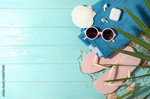 Flat lay composition with earbuds and beach objects on light blue wooden background. Space for text
