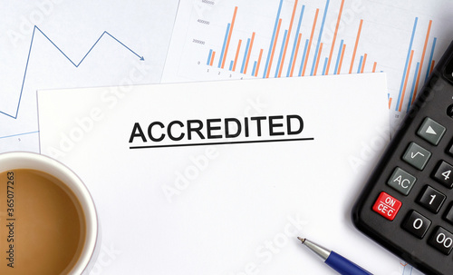 Photo Accredited document with graphs, diagrams and calculator and a cup of fragrant c