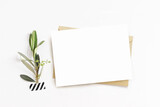 Feminine stationery, desktop mock-up scene. Blank horizontal greeting card, craft envelope and washi tape with green olive branch.White table background. Flat lay, top view. No people.