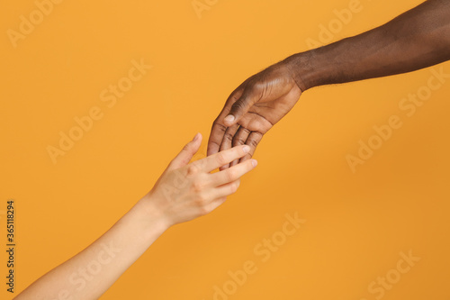 Hands of Caucasian woman and African-American man reaching out to each other on color background Canvas Print
