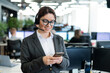 Beautiful caucasian woman in headset is holding a mobile phone while standing in open space office. Friendly female helpdesk operator browsing the screen of a smartphone in the workplace.