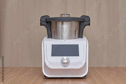 front view of a food processor, on a wooden table