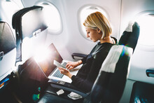 Blonde Female Tourist Checking Incoming Notification On Smartphone Sitting On Seat Of Airplane With Netbook.Young Businesswoman Share Media From Telephone On Laptop Computer During Plane Flight
