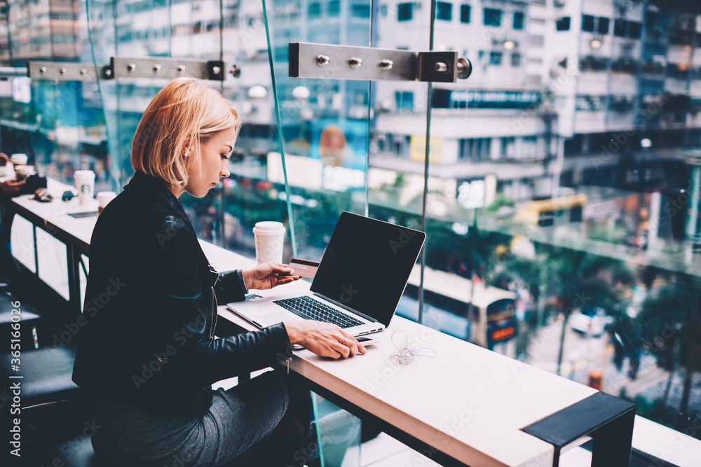 Fototapeta Blonde businesswoman with credit card in hand sitting in cafe for freelance with cityscape and making payment online on website on laptop computer.Student doing transaction on netbook via internet