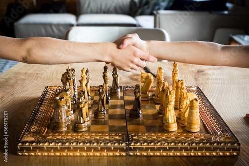 Shaking hands as a sign of good honest and chess Canvas Print