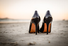 Close-up Of Shoes On Beach Against Sky During Sunset