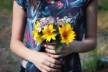 Midsection Of Woman Holding Yellow Flower In Field