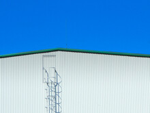 Rooftop Of Corrugated Iron Plated Industrial Hall With Ladder To Rooftop Door.
