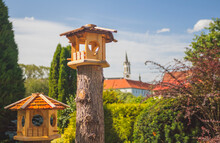 Wooden Bird Feeder In The Garden, In The Background The Castle Tower