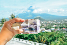 Cropped Hand Holding Paper Currency Against Mountain
