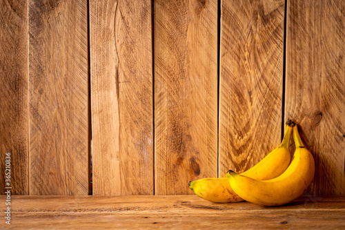Obraz Brown wooden wall with two yellow bananas and copy space - fototapety do salonu