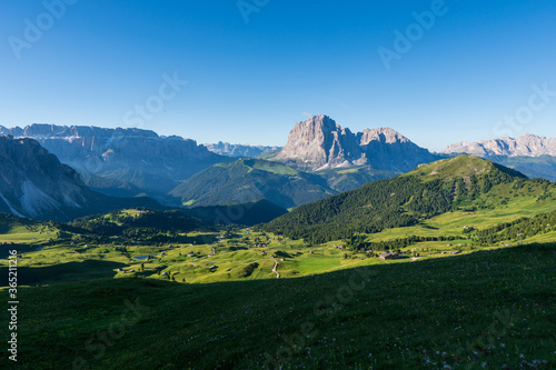 Fotomural Epic mountainlandscape in Puez Odle, Dolomiti / Dolomites Alps in Italy, Seceda area, with Sass Rigais in background, small traditional cottages in green meadow and hiking trail path