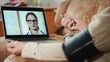 Elderly woman consults doctor via webcam, measures blood pressure