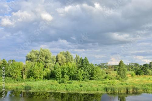 Fototapeta River meanders on a cloudy day, clouds in the sky. obraz na płótnie