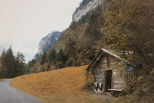 Old Wooden Shack On The Side Of A Country Road At The Foot Of A Mountain