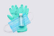 flat layout of hygiene items - latex gloves, mask and hand sanitizer over light grey background