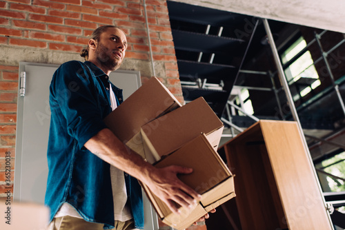 low angle view of man holding boxes while moving in new office Wallpaper Mural