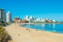 People On Beach By Buildings Against Clear Blue Sky