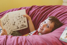 Portrait Of Boy With Comic Book Lying On Bean Bag