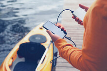 The Guy Holds A Portable Charger With A Smartphone In His Hand. A Man Against The Background Of Water And A Kayak Charges The Telephone With Power Bank. Concept On The Theme Of Tourism.