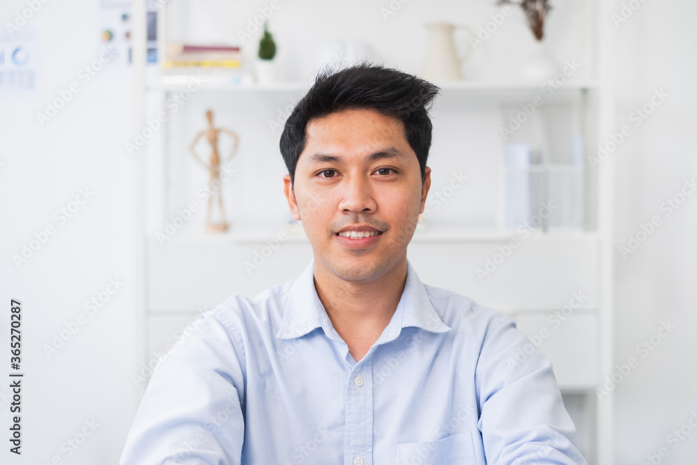 Fototapeta Screen of Asian businessman talking while video call or virtual meeting in office, front view look at laptop web camera